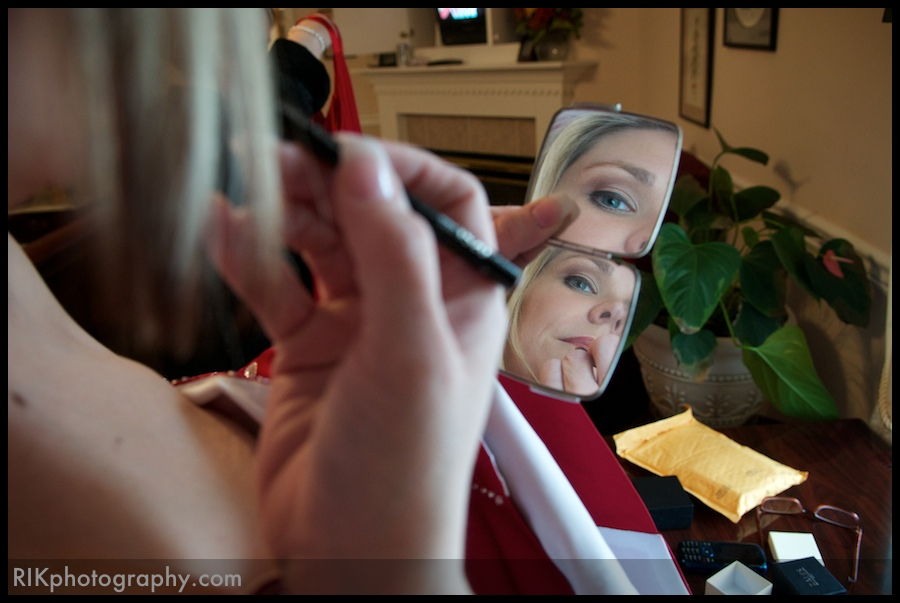 Bride applying makeup before her wedding