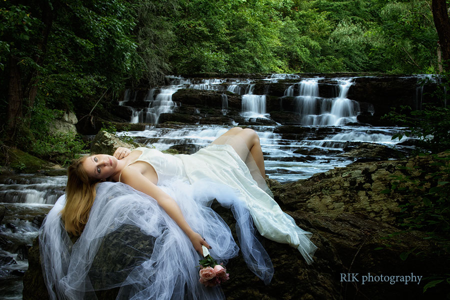 bride lying on a rock by a waterfall
